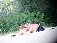 A hot couple of sexy nudist lovers are lying stretched on their bellies and do not see the cameraman shooting their butts from behind